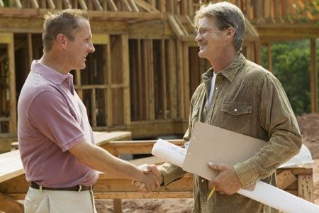 Tow men shaking hands in front of a house that is under construction,