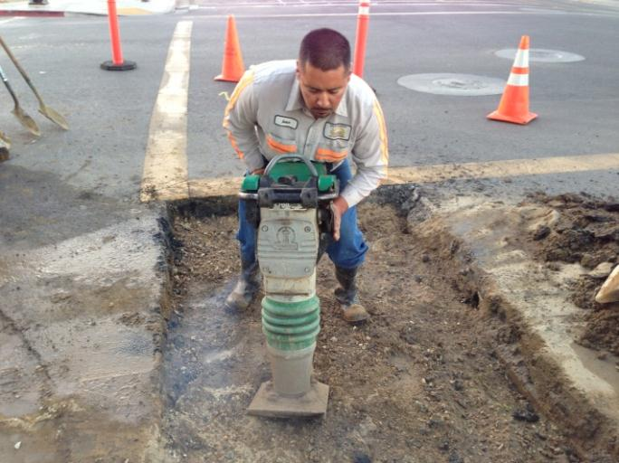 A man with a jack hammer working on a road.