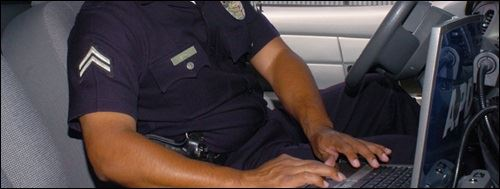A police officer using a computer in his car.