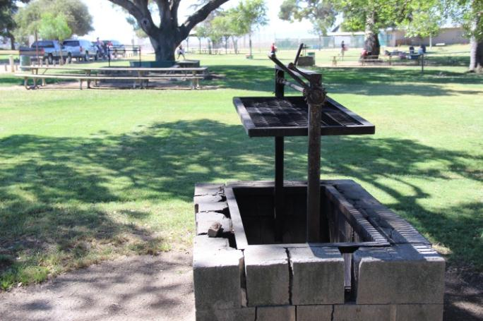 A grill made up of a steel grate hanging over a barbecue pit.