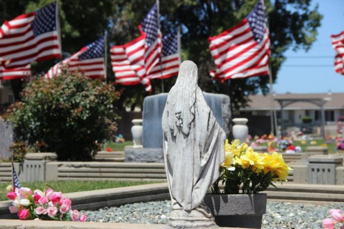 A grave monument with American flags in the background.