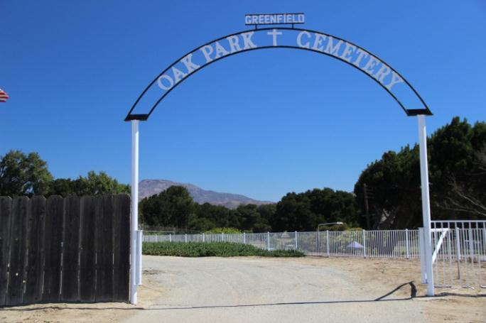 The entrance to the cemetery. A large white sign shaped like an arch.