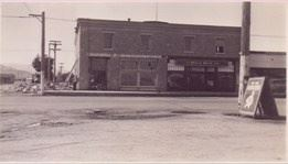 A black and white photo of a store on the corner.