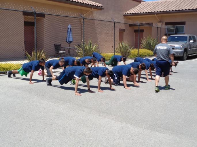 Young men and women doing push ups outside.
