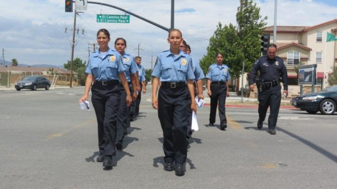 Young women marching in police uniforms.