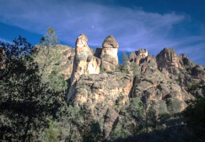 Large rock pinnalces with trees on it.