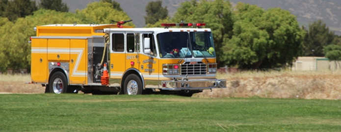 A yellow fire truck in a field.