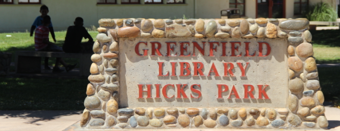 "A stone sign reading ""Greenfield Library Hicks Park."""