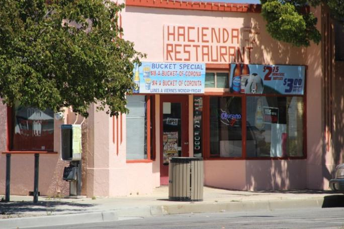 The front of the Hacienda Restaurant. It is a pink building with trees in front of it.