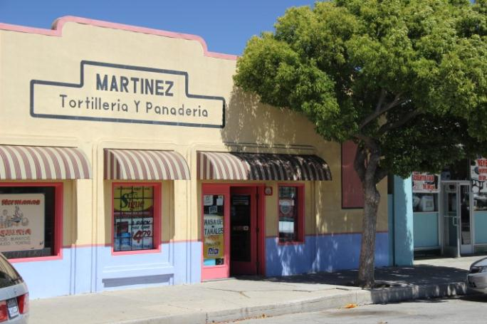 A store front for a store called Martinez. There is a green tree in front of the store.