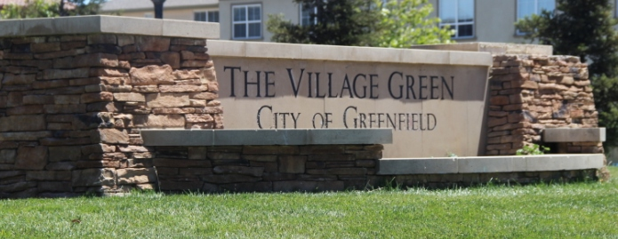 "A large stone sign that reads ""The Village Green City of Greenfield."""